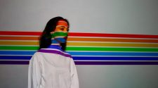 Woman standing in front of wall painted with rainbow stripes
